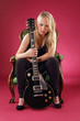 Beautiful blond sitting with electric guitar