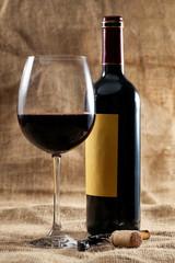Botella de vino tinto y copa llena