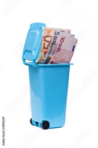 Mülltonne mit Geld auf weißem Hintergrund isoliert