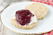 Scone with goat cheese and jam on a plate closeup