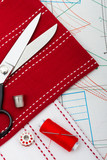 sewing tools and fabric against sheet of professional clothing p