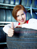 Female apprentice showing thumb up for tire changing