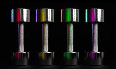 Four Dumbbells on Black Background