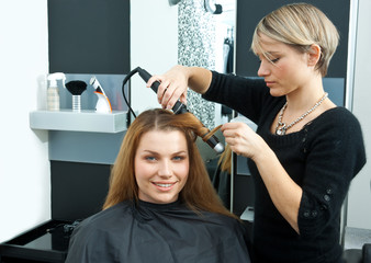 hair stylist curling woman hair in salon