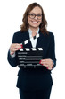Gorgeous corporate woman holding a clapperboard