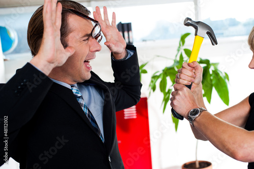 Woman threatening her boss, holding hammer. Poster