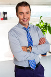 Young manager in formals standing with arms crossed