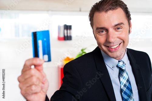 Handsome male executive holding cash card