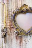 Vintage frame with hanging keys on a wooden background