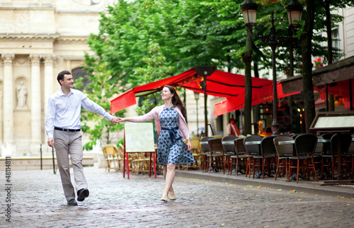Couple walking in Paris near an outdoor cafe
