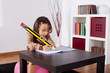 Little girl writing with a giant pencil