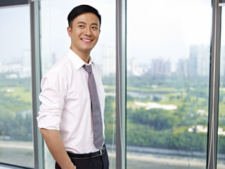 young asian businessman standing by the window