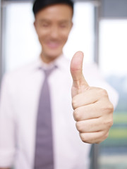 young asian businessman showing a thumbs up sign