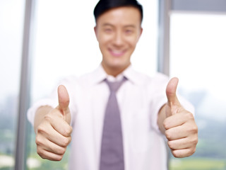 young asian businessman showing two-thumbs-up sign