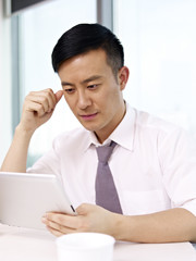 young asian businessman looking at tablet computer in office