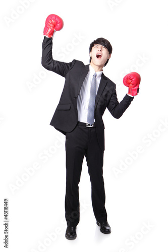 Businessman wearing boxing gloves in a victory pose and raise hi