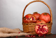 Ripe pomegranates on basket on wooden table on grey background