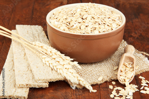 Oat flakes in brown bowl on the table