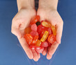 Hands full of sweets on blue background