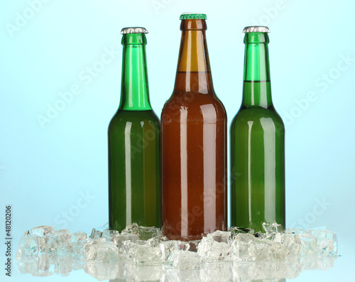 Beer bottles in ice on blue background