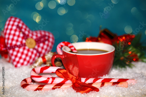 Hot tasty drink in red cup with Christmas candies