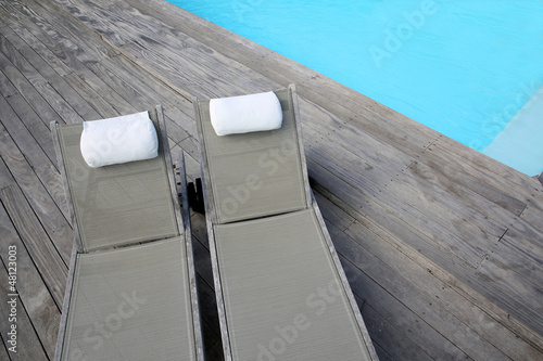 Closeup of long chairs set by resport pool