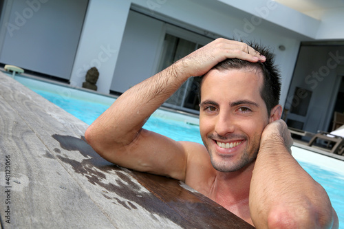 Portrait of smiling guy in swimming pool