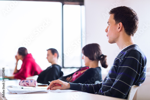 young, handsome male college student sitting in a classroom