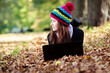 Beautiful young girl with laptop in autumn park. European Girl
