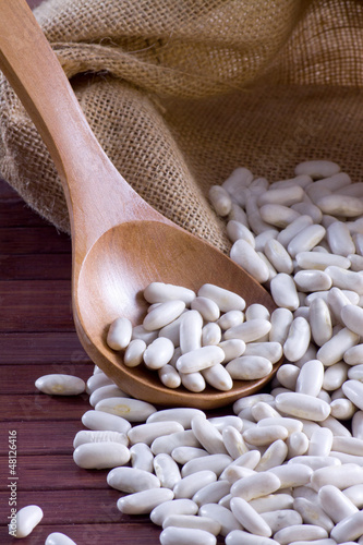 White beans - Cannellini (legumes) in a wooden spoon and bag