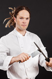 Handsome chef sharpening his knife