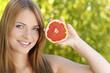 Junge Frau zeigt eine Grapefruit im Grünen