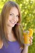 Junge Frau lächelt mit einem Glas Orangensaft