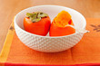 Persimmons in bowl with spoon