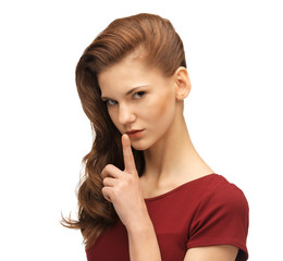 teenage girl in red dress with finger on lips