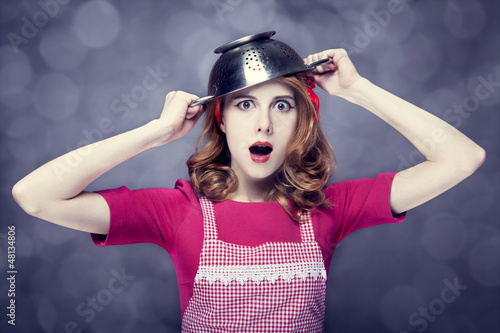 Redhead housewife with colander over head