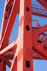 Red part of bridge frame isolated on blue vertical closeup