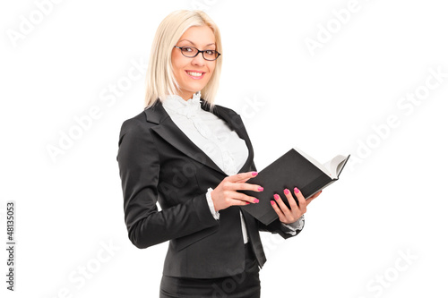 A blond female teacher holding a book