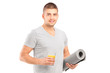 A male holding a glass of juice and a mat after an excerise