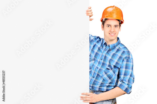 A male worker with helmet posing behind a panel