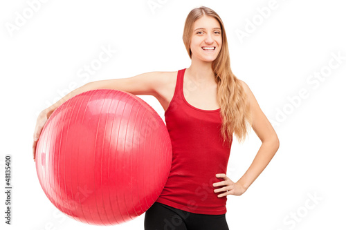 A young female athlete holding a pilates ball