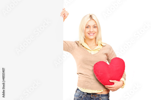 A young female holding a blank panel and red heart