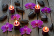 Spa stones orchids and candle on wooden boards