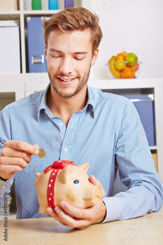 Mann steckt Euromünze in Sparschwein
