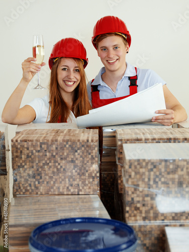 Young couple celebrate her project planning in a building lot