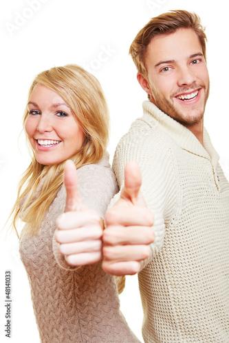 Lachendes Paar hält Daumen hoch