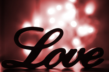 Love sign on red with light sparkles