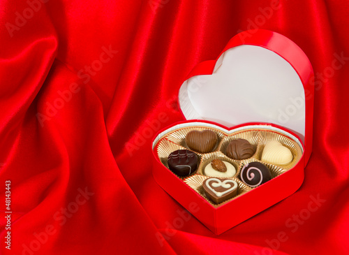chocolate pralines in golden box over red silk