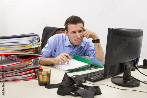 Confused accountant at work with huge piles of documents.