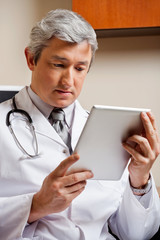 Doctor Looking At Digital Tablet